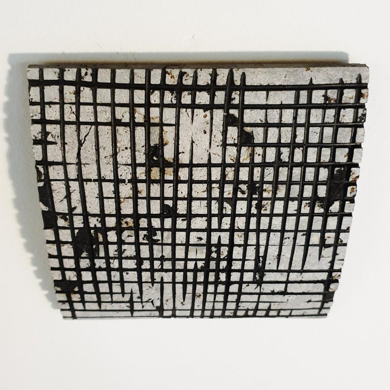 o.T. (Bk15Cr) is a unique small size contemporary modern wall sculpture painting relief by German artist Dieter Kränzlein. The relief is made from limestone and the carved pattern is finished with a thin layer of black ink that has penetrated into
