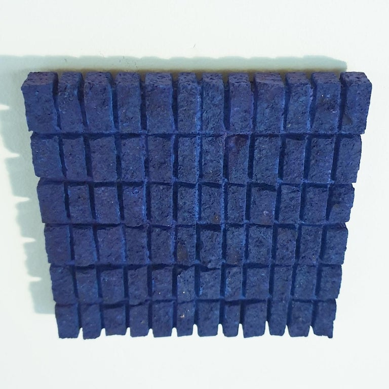 o.T. (Bl15Rc) is a unique small size contemporary modern wall sculpture painting relief by German artist Dieter Kränzlein. The relief is made from limestone and it is finished with a thin layer of blue ink that has penetrated into the limestone. Due