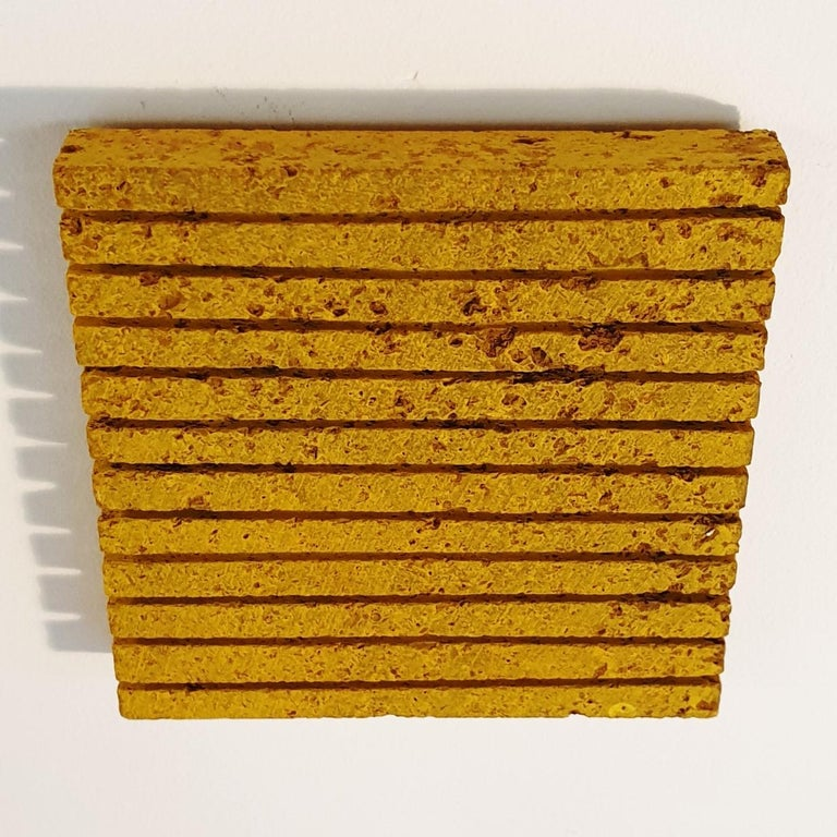 o.T. (Yw15Ln) is a unique small size contemporary modern wall sculpture painting relief by German artist Dieter Kränzlein. The relief is made from limestone and it is finished with a thin layer of yellow ink that has penetrated into the limestone.