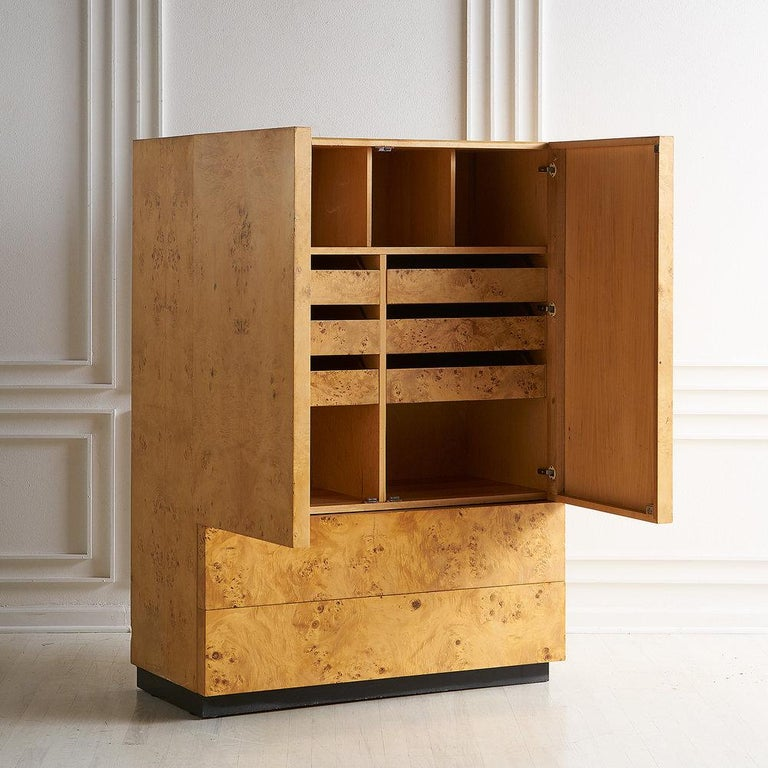 A sophisticated burl armoire in a beautiful light finish. There are two deep bottom drawers while the large upper doors conceal cubby and shelf space, and six small drawers. Black plinth base.  Dimensions: 42