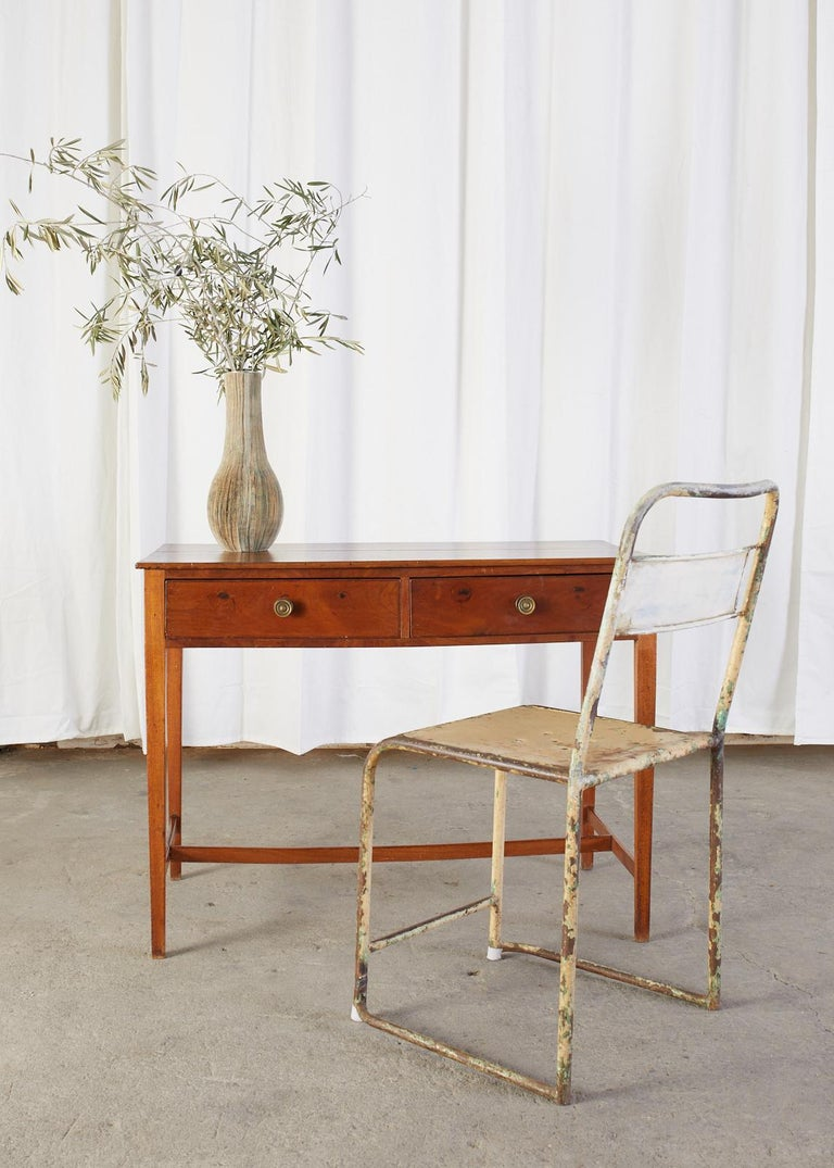 19th century mahogany writing table or desk made in the federal style in a diminutive scale. The table is fronted by two storage drawers with round brass pulls. Supported by elegant tapered legs conjoined by an H shaped stretcher. The desk showcases