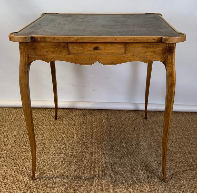 A small mid-20th century French style games table with tooled green-brown tooled leather top above single drawer resting on delicately carved legs.