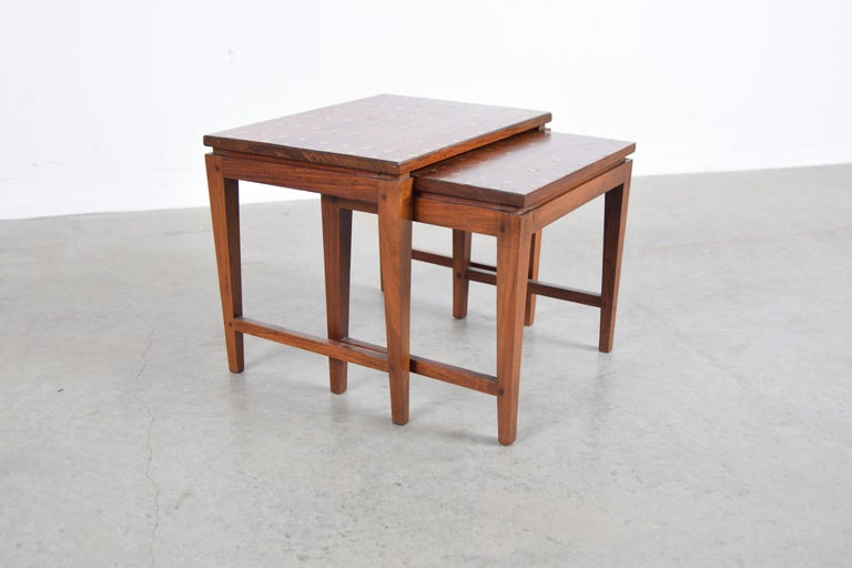 Diminutive set of two solid teak nesting tables with traditional Tarkashi (brass inlay) tops, designed by Indian designer Leela Shiveshwarkar, circa 1960.  Tables measure as follows: Larger table: 14 3/4