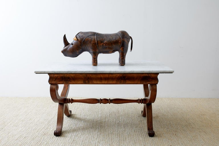 Mid-century English leather footstool in the shape of a rhino designed by Dimitri Omersa for Abercrombie and Fitch. Good solid construction with a beautifully aged patina on the thick leather. Intact with all eyes, ears, horn, and tail. From an