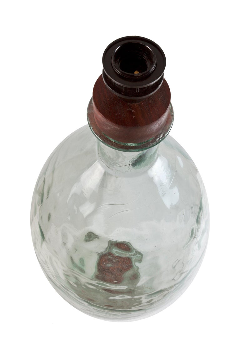 A very unusual pale green, dimpled demijohn distillery bottle. Great size and scale. I had a stopper made with an electrical light socket so that it could be used as a table lamp and takes a regular size light bulb. To use or not. Makes a great
