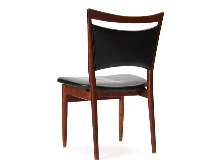 A sculptural oak framed Model 86 dining chair by Finn Juhl. The Scandinavian Modern style chair features a rounded teak handle back and original black leather upholstery. Crafted in Denmark, circa 1950s.  Finn Juhl was first and foremost famous for