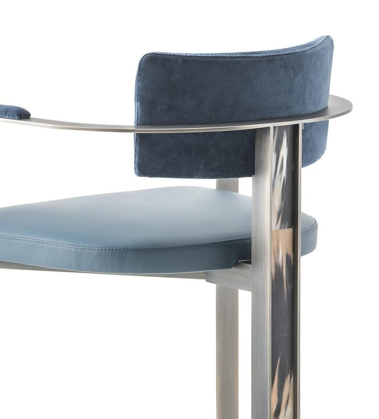 This stunning dining chair is balanced by an open, semi-circular frame made of bronzed metal with upholstered back and seat cushions that define rather than distract from the overall look. The seat and rectangular backrest feature a sophisticated