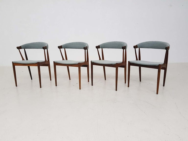 Set of 4 rosewood dining chairs by Johannes Andersen for Andersens Møbelfabrik, designed in Denmark in 1969.  This Danish modern set from the midcentury are made of beautiful rosewood and are newly upholstered in mint green fabric.   They remind us
