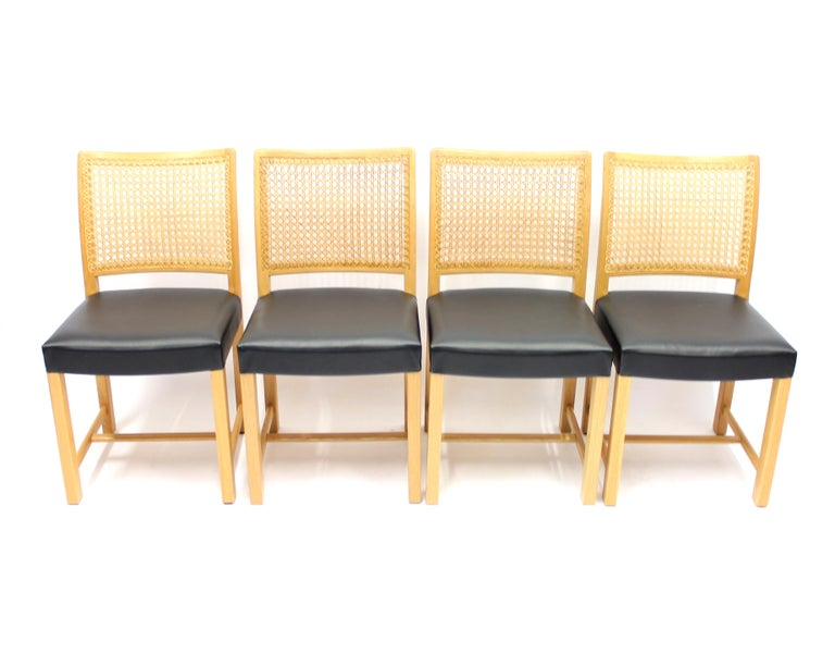 Set of 4 dining chairs designed by Carl Gustaf Hjort af Ornäs for Mikko Nupponen in the 1950s. Frame and legs of solid oak, cane back and new black leather upholstery on the seats.