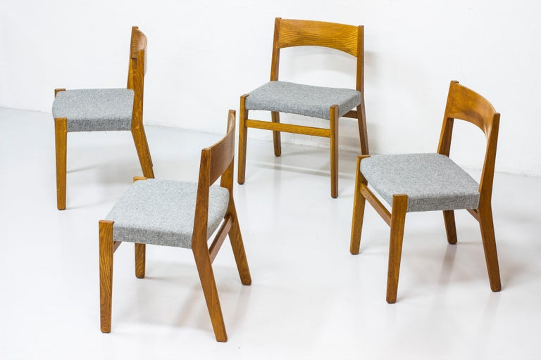 Set of four dining chairs designed by John Vedel Rieper. Produced in Denmark by Erhard Rasmussen. First presented at the Copenhagen Cabinetmakers' Guild exhibition in 1957. Made from solid oak with new