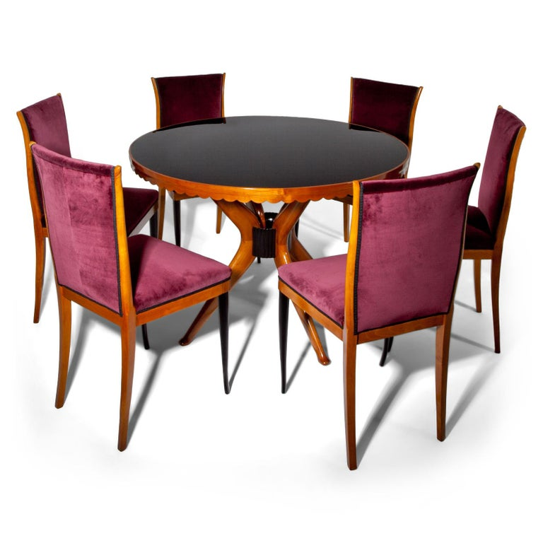 Set of six dining room chairs with ebonized front legs and Bordeaux colored upholstery on seat and backrests.