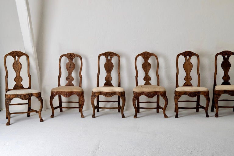 A set (assembled) of six dining chairs made during the Rococo period 1750-1775 in Sweden. Beautiful raw patina with stunning carvings. Cabriole legs ending in claw and ball feet.