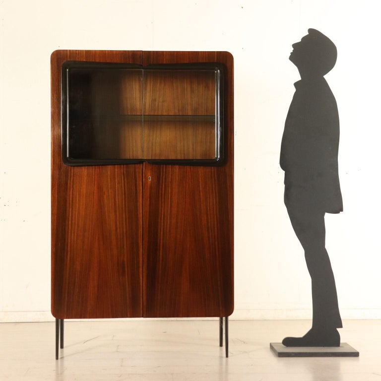 A dining room cabinet with hinged doors made of wood and glass. Designed by Ico Parisi (1916-1996) for Fratelli Rizzi. Inner shelf, wooden drawers and glass shelf. Mahogany veneer, solid wood with ebonized molding. It comes with Rizzi authentic.