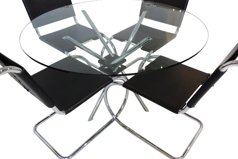 A set of Mies van der Rohe black leather and chrome chairs produced by Knoll International matched to a Takehiko Mizutani MZ59 table  These chairs are a design icon being one of the very first cantilever design chairs ever designed by van der