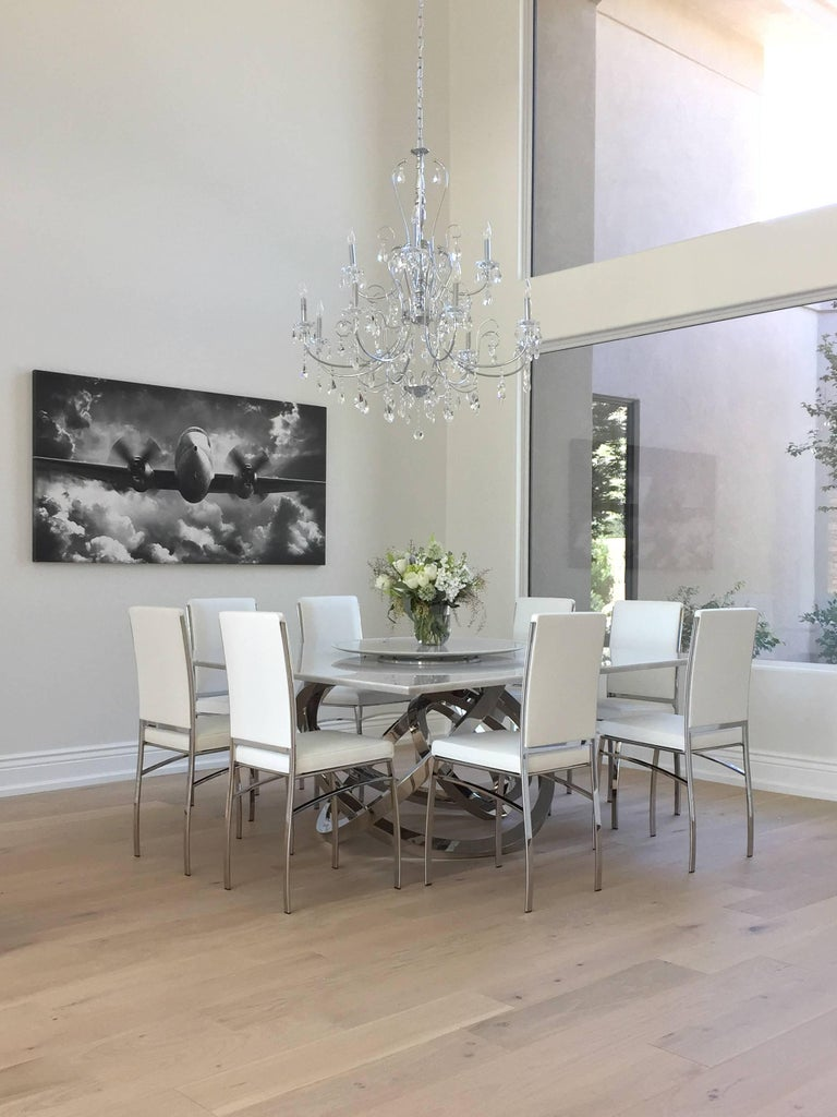 The table 'Perseo' is an important dining table with structure in mirror polished stainless steel and top in Calacatta marble, origin: Tuscany. Dining table dimension: L 175, W 175, H 75 cm. Every single bangle is welded and highly polished by hand.