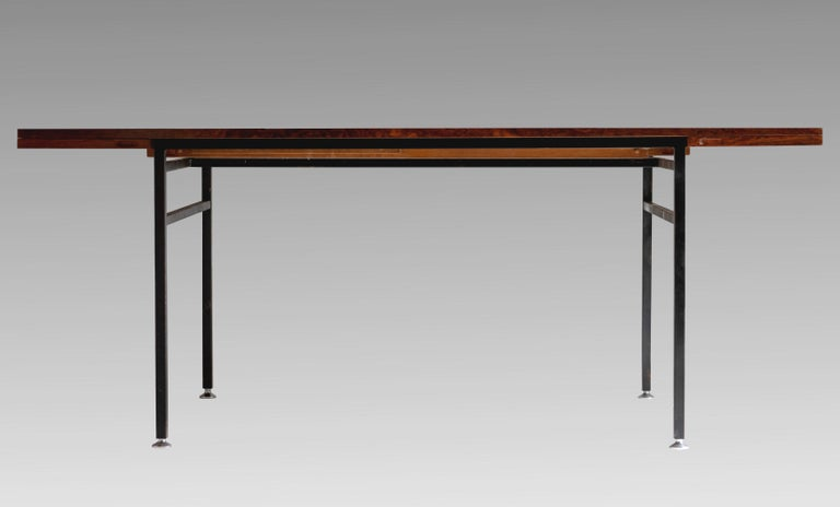 Alain Richard, (1926-2017) Dining table in rosewood with double extension, series 800, edited by Meubles TV (J.Tricoire & R.Vecchione), France, 1958. Base in black lacquered metal, adjustable chromed legs. Labelled under the tray. In very good