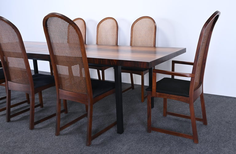 A beautiful Mid-Century Moderndining table and chair set designed by Milo Baughman for Directional. The table is made of gorgeous teak, rosewood, and walnut and opens up to 112 inches long. A great set for family gatherings and holidays. The set