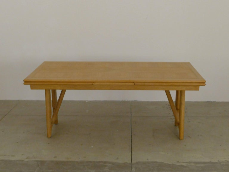 This impressive piece of furniture is both in perfect condition but also created with the stylish lines that the creators are known for. The white oak has no defects. The lacquered top has two leafs which slide out from under it and will allow you