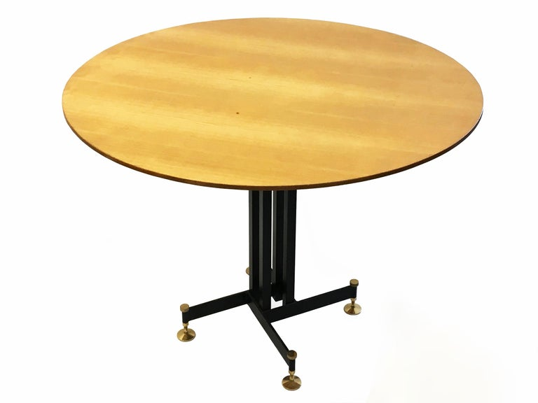 Italian dining table attributed to Ignazio Gardella comprises a black enameled steel base with brass feet that can adjust up to 2 inches (5 cm) for height and leveling purposes, that supports a round wooden top.