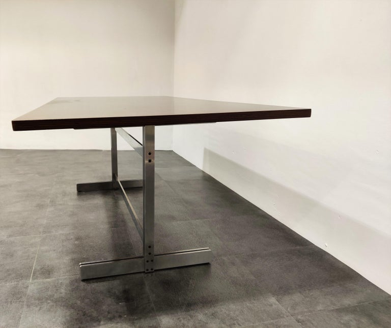 Exclusive and timeless designed dining table by Jules Wabbes for Mobilier Universel.  This table has a beautiful modernist design and features a fully restored wooden top mounted on a steel base.  Can be used as a dining table, conference table