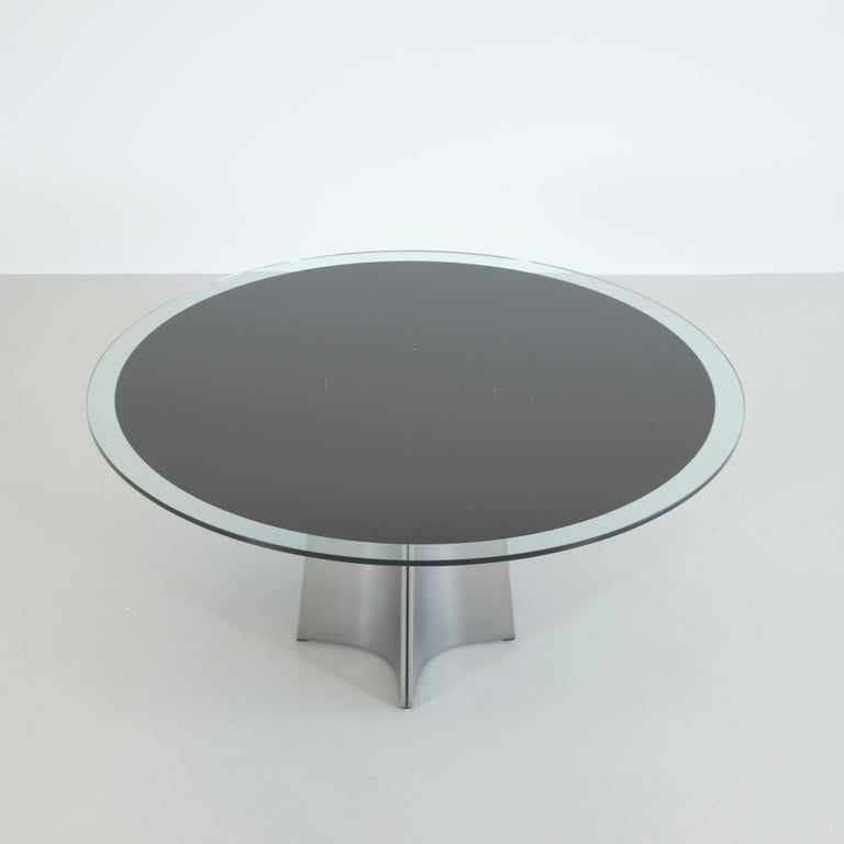 Round pedestal dining table designed by Luigi Saccardo. Italy, ARRMET, circa 1973.  Brushed aluminum base and the original round glass top with black center underlay. The curved metal producing a star-base. An iconic piece by the Italian Modernist