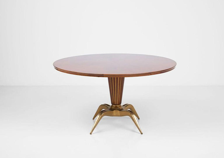 Dining table, a unique piece designed by Melchiorre Bega for the house of Dr. Pietro Caliceti in Bologna, Italy. Structure in Italian walnut with round top and extensions. Base in brass casting partly finished with walnut strips. Expertise signed by
