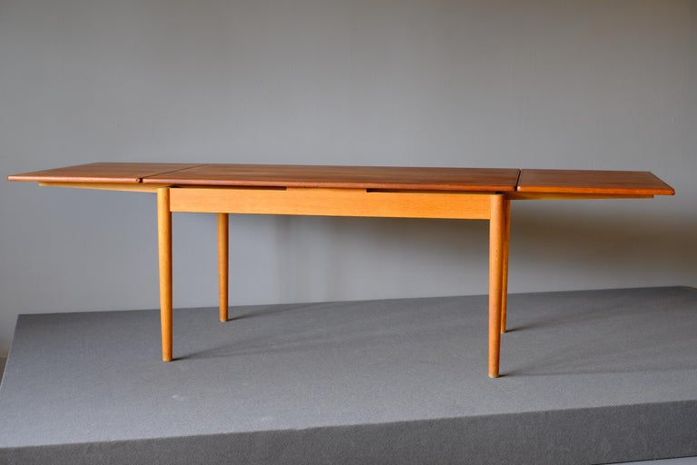 Dining table Model AT 316 designed by Hans Wegner for Andreas Tuck. It is in teak and has 2 pull-out / pull-out leaves which hide under the top. The leaves are cleverly integrated into the top when they are not in use. The table has round slightly