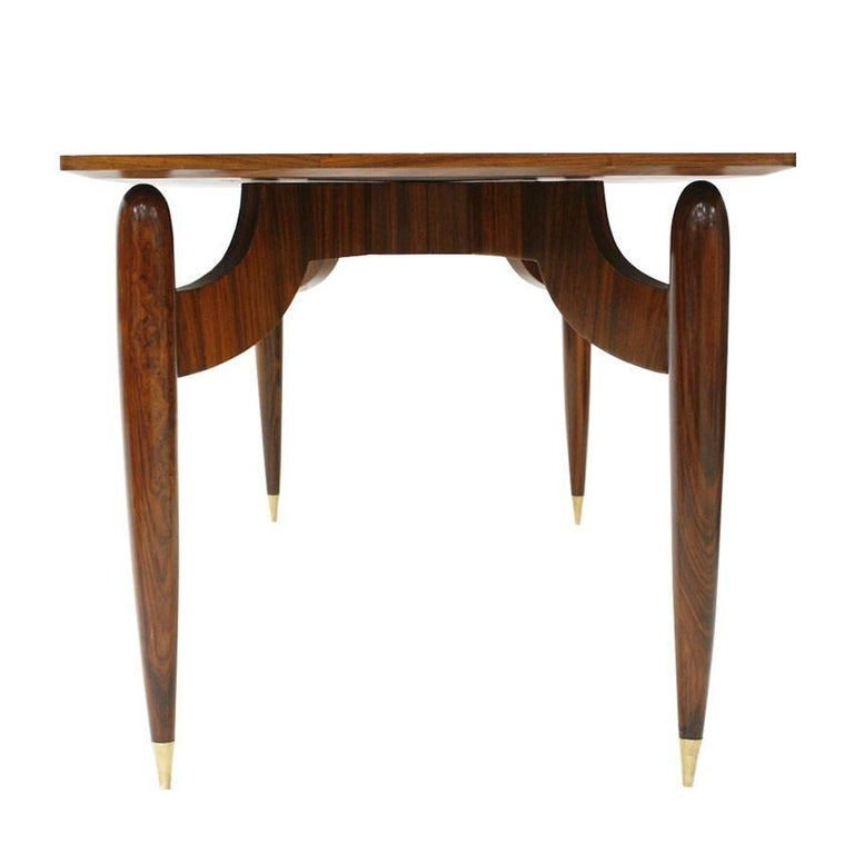 Dining table with legs flown to a central axis with solid wood structure and covered in rosewood. Legs with brass finish, Italy, 1950.