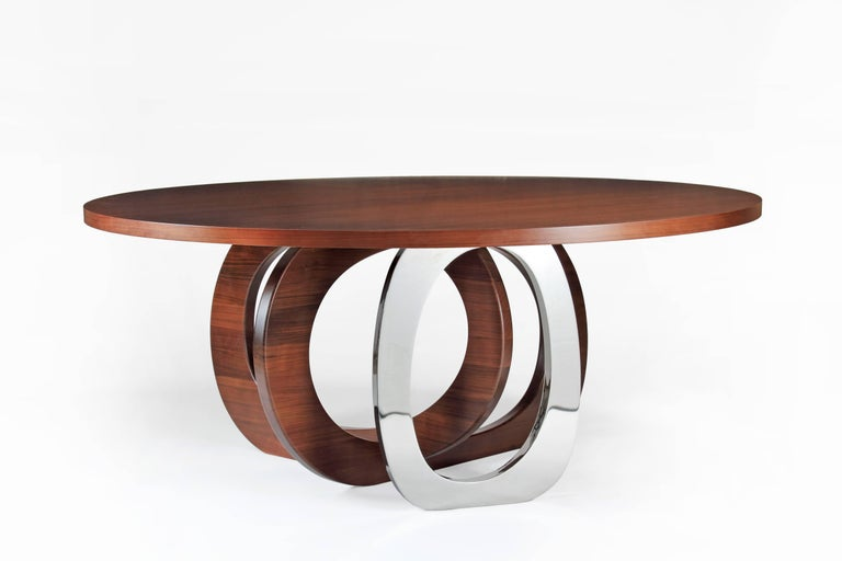 The 'Bangles Kelowna' table has a circular top, two rings in solid wood and a single ring in mirror polished stainless steel AISI 316. Dimensions: D 180, H 75 cm. Each table is hand signed and numbered by the artists technique: Engraved. 100%