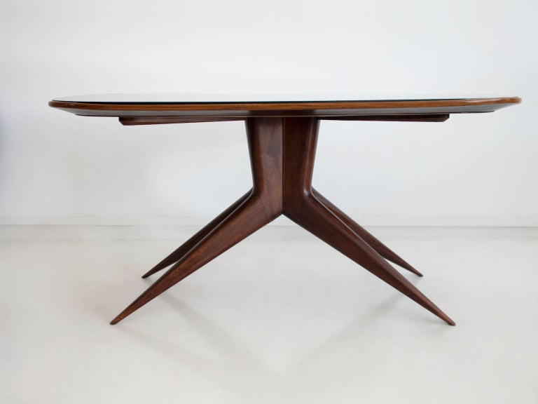 Rectangular dining table with round corners, manufactured in Italy, circa 1950. Structure made of wood, top of dark stained crystal.