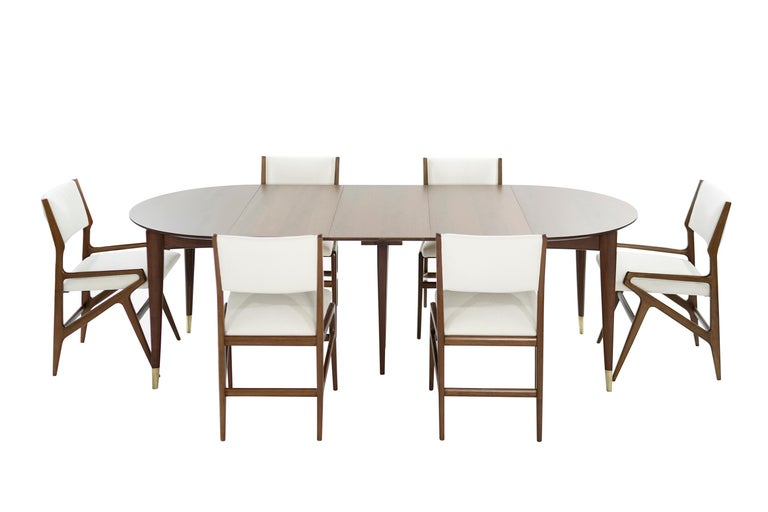 Extremely rare dining room set, designed by the iconic Gio Ponti for M. Singer & Sons, circa 1950-1959.  Walnut dining table features Gio Ponti's signature brass sabots, four 16
