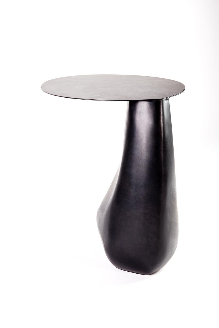 A signature piece from our stone collection, the expertly hand-sculpted Dionis Side Table evokes the subtle curves and contours of tumbled stones shaped by the ocean. This seamless, blackened steel table presents as sculpture yet functions as a