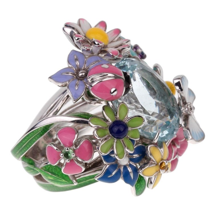 A magnificent Dior ring from the Diorette collection - an ode to the flowers and fantasies of the Christian Dior garden. Crafted in 18k white gold, the ring showcases a large Aquamarine surrounded by Amethyst, Pink sapphire, Yellow sapphire, and