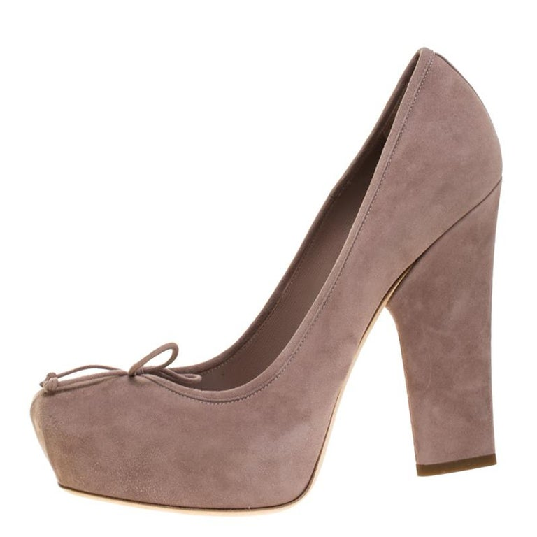 Look chic and make an elegant style statement with this pair of suede pumps. From the house of Dior, this pair is designed with petite bows on the vamps and high block heels. In a remarkable shade of beige, you can wear these pumps for both work and