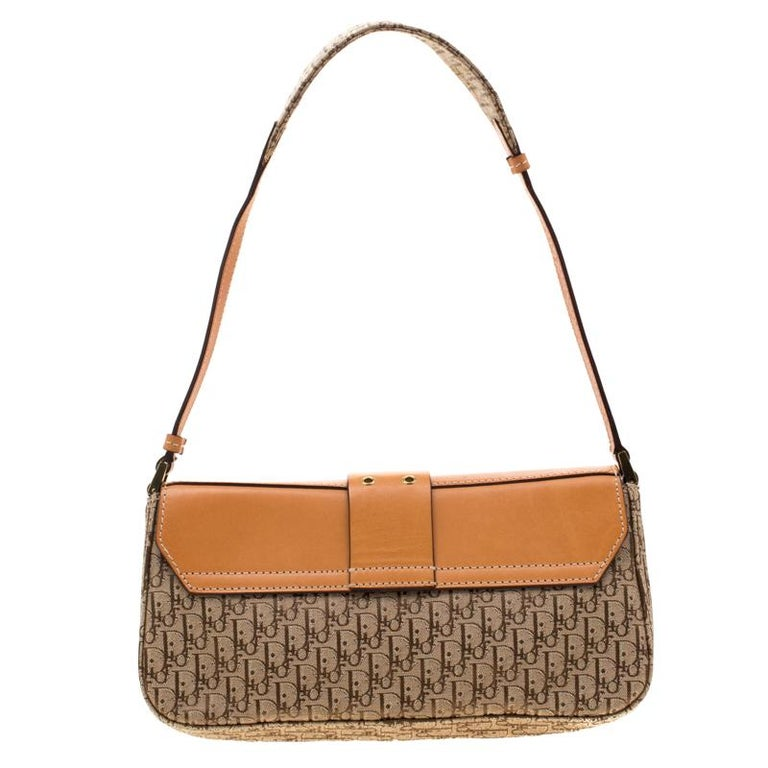 Add a subtle style and elegance to your look with this Street Chic shoulder bag from Dior. It comes crafted with the signature Oblique canvas and accented with tan-coloured leather details. It features a front flap attached to which is a belt strap