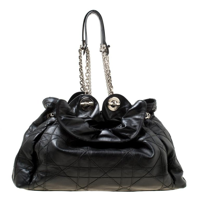 This stylish Le Trente hobo from Dior has been crafted from black leather and styled with their signature cannage pattern. The bag features dual chain straps with leather shoulder rest, a CD cutout charm, a drawstring closure and protective metal