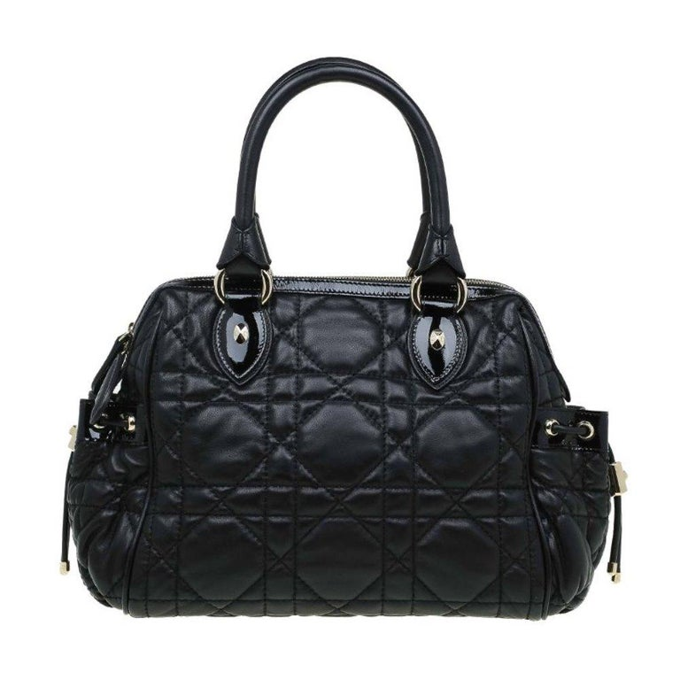 Made of leather with the signature cannage quilting, this Dior satchel is easily recognised. It has two rolled top handles so it can be draped easily over the arm and silver tone hardware. In addition to a spacious main compartment, it also has two