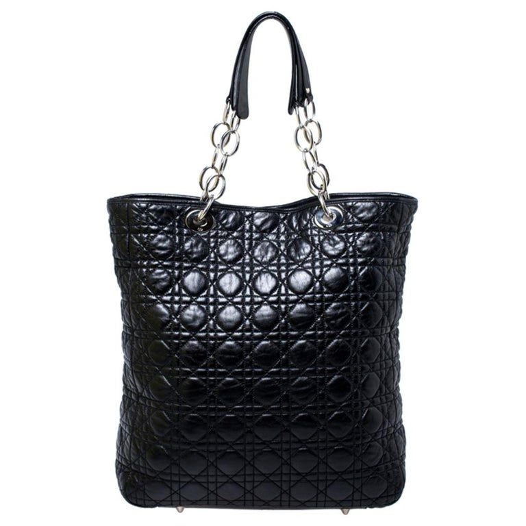 This shopper tote from Dior is a timeless piece. The bag is crafted from luxurious black leather and has the cannage pattern. It features double top handles, protective feet at the bottom and Dior letter charms in silver tone. A buttoned closure