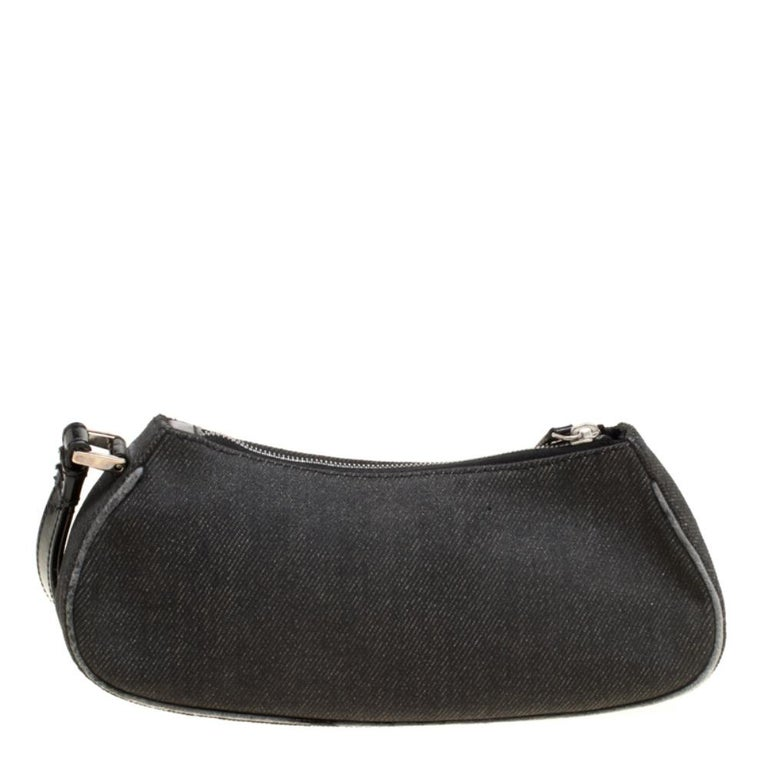 Cute and compact, this Motorcycle Rockabilly wristlet clutch from Dior is perfect for your chic style. The black creation is crafted from denim and leather and features a round motif that resembles a red light. It has a top zip closure that opens to