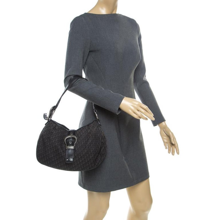 This stylish Dior creation is the ideal companion. Beautifully crafted from signature Diorissimo canvas the bag is held by a single leather handle. The front buckle closure secures a nylon interior sized to hold your necessities. This bag will