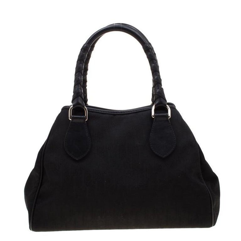 This charming satchel features durable black diorissimo canvas. Accentuated with silver-tone hardware, it comes with two top handles. Lined with nylon, its interior can easily hold all your essentials. To make a remarkable style statement, this