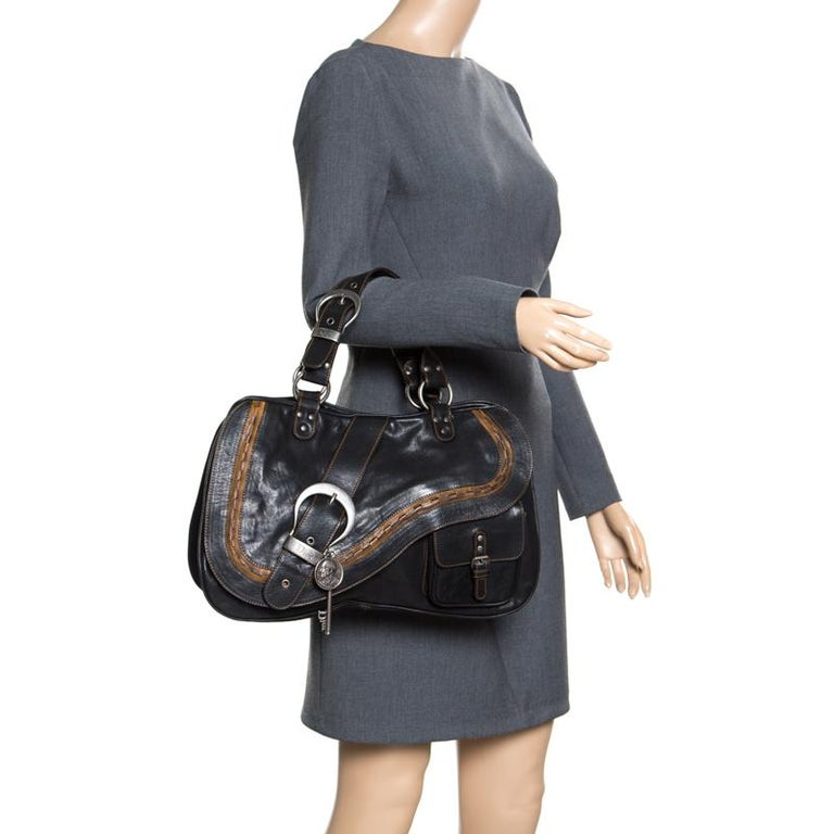 Inspired by the shape of a saddle, the popular rustic style Dior Gaucho shoulder bag is a unique bag to own. The Gaucho bag's exterior is made from black leather that folds over to resemble an old western saddle. It is accented with an adjustable