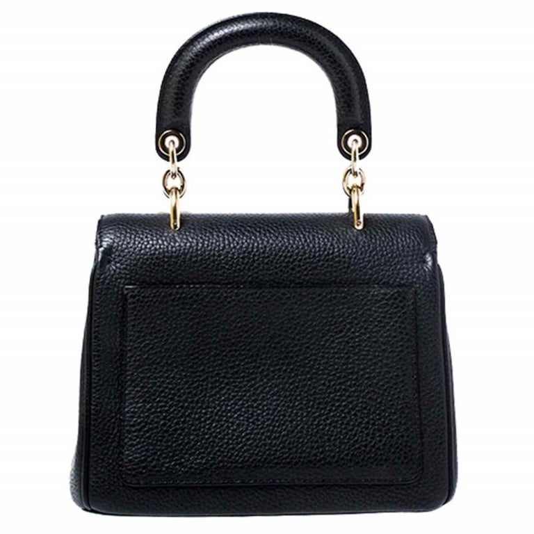 Flap bags as gorgeous as this one from Dior will never go out of style. This beauty has been meticulously crafted from leather and equipped with a single rolled top handle, protective metal feet at the bottom and the Dior letter charms. The flap