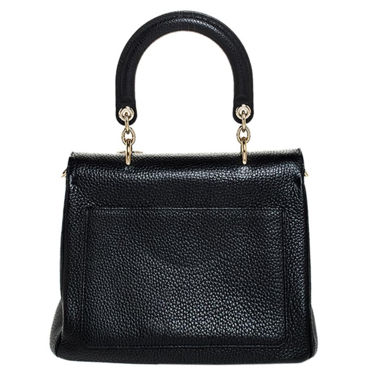 This Be Dior bag from the house of Dior is sure to add sparks of luxury to your wardrobe! It is crafted from leather and features a chic silhouette. It flaunts a single rolled top handle with attached 'DIOR' letter charms and comes equipped with