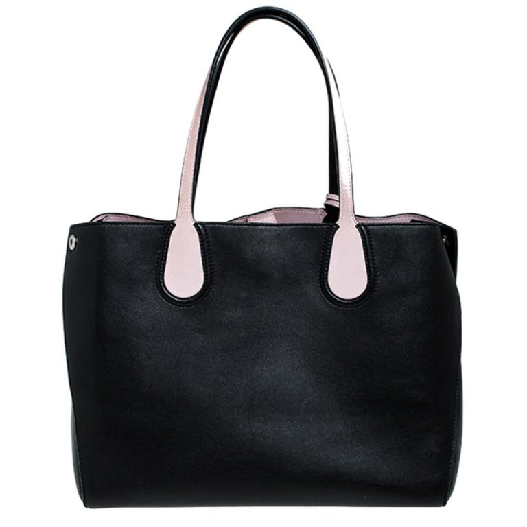 This Dior Addict tote is a perfect companion for daily use. Crafted from leather in black with pink leather details, it is enhanced with silver-tone hardware. The bag features two flat handles, studs to secure its bottom, and pink-tone Dior charms.