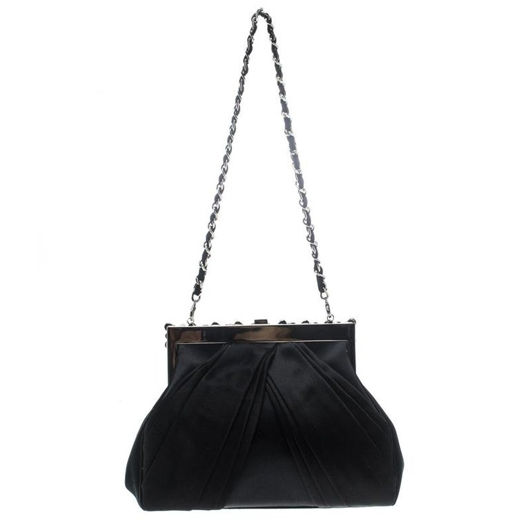 Have all eyes on you when you flaunt this stylish clutch by Dior. Crafted from black satin it has a structured frame enhanced with embellishments and a bow on the front. It has a satin lined interior with an open compartment and is completed with a