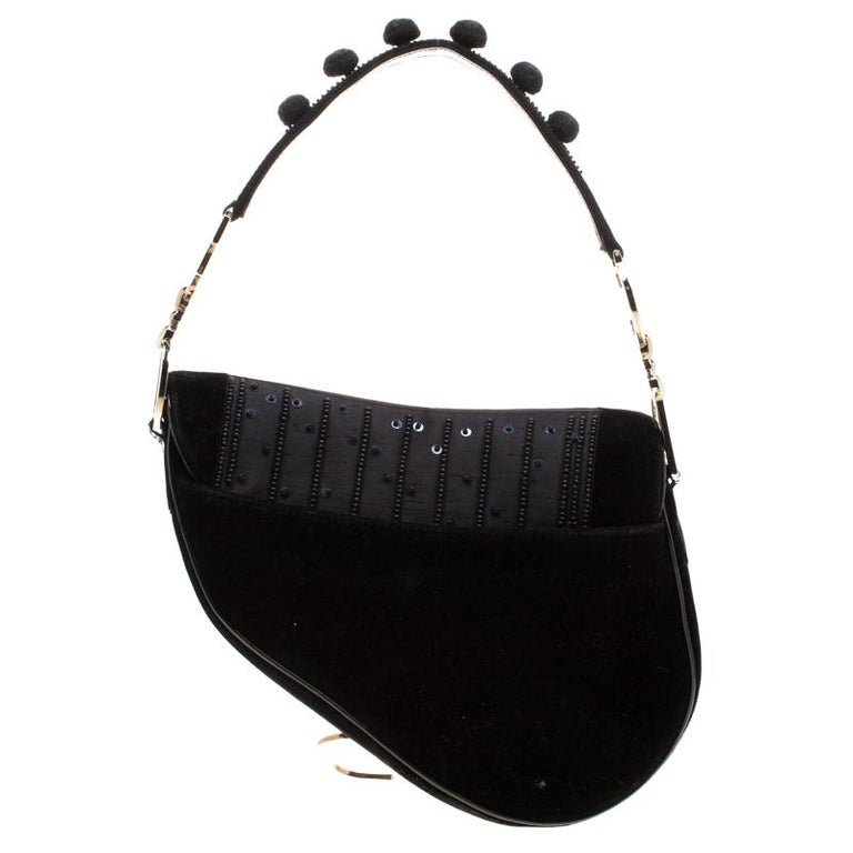 Originally designed by John Galliano, the Dior Saddle bag made a smashing comeback in the year 2018. Here, we have a splendid version of the bag. It is made from velvet, nylon and patent leather and embellished with pom poms. A single handle and a