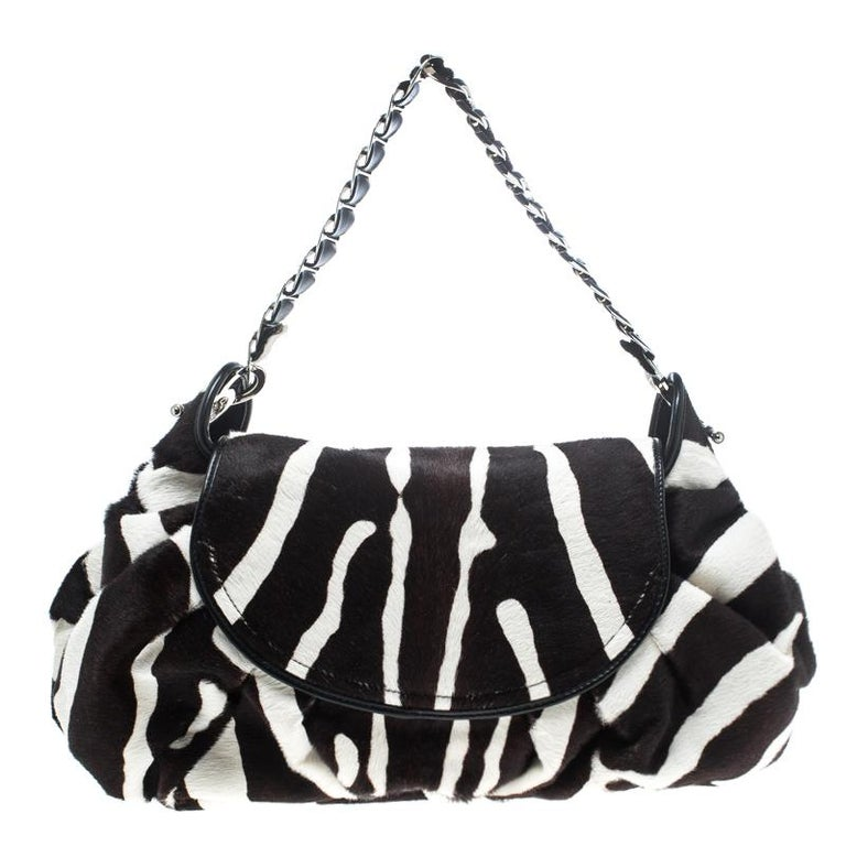 Classic, chic and very sophisticated, this Dior hobo is sure to enchant and cast a spell on you. The creation is crafted from calf hair and features a black and white animal print on it. It flaunts a front flap closure that is detailed with