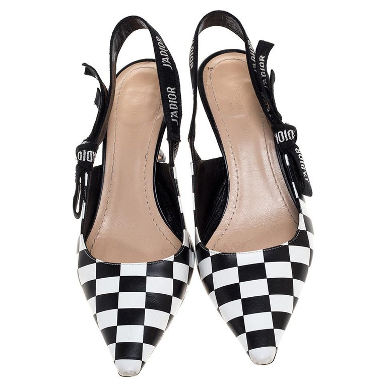 You'll definitely gather admiration wherever you go when you step out in these lovely sandals from Dior. The black and white checked pair is crafted from leather and feature pointed toes and J'adior ribbon slingbacks. The pumps are complete with