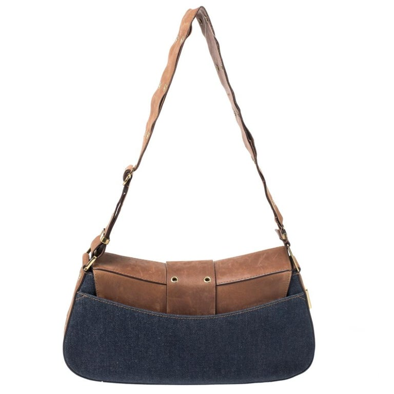 To make a remarkable style statement, this handbag by Dior is just what you need. Crafted in Italy, it is made of quality denim fabric and leather. It comes in lovely hues of blue and brown. This chic shoulder bag is held by a single handle, front